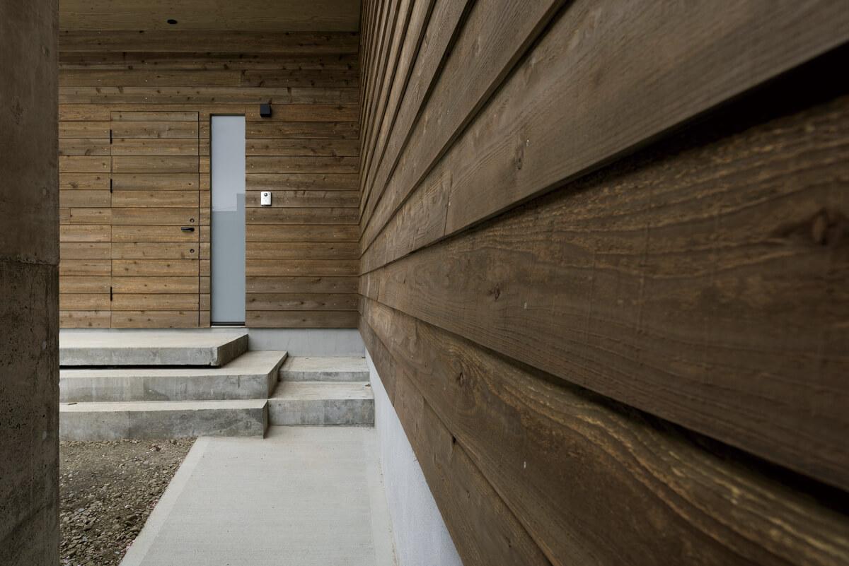 玄関ドアは、道南スギ仕上げの外壁と一体化させたデザインに