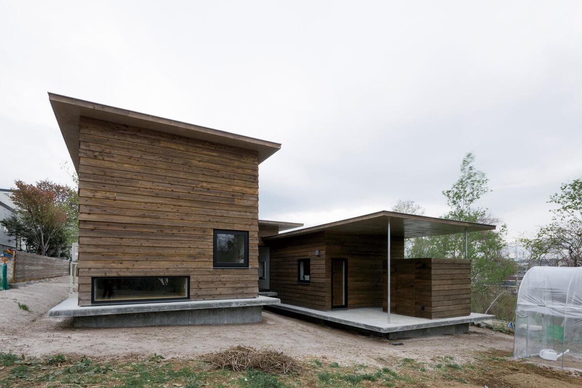 傾斜のある敷地形状を生かしたスキップフロアの平屋。屋根付きの土間の一角には、農作業小屋を設けた