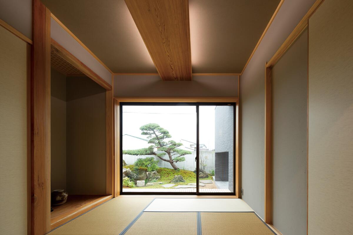 親世帯の玄関脇に設けられた和室はゲストルームとしての用途も。面する庭も和室に合わせ純和風に