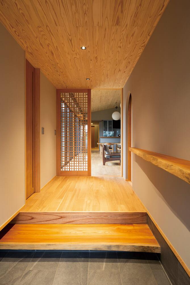 玄関を入ると建物奥の方向に一直線に伸びる親世帯の動線。能舞台のような劇的な空間構成だ
