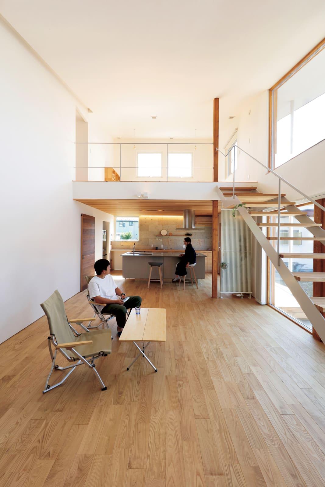 片流れ屋根の形状を活かしたダイナミックなLDKは吹き抜けで開放感いっぱい。白壁と木の空間に白のスケルトン階段が映える
