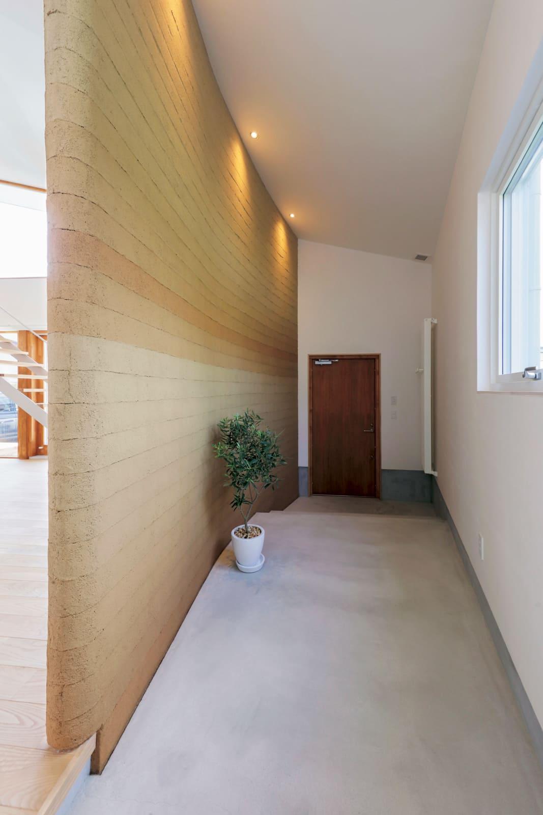 リビングと玄関の土間スペースの間仕切りも土壁で。部屋に入る前に気持ちをリセットできる空間