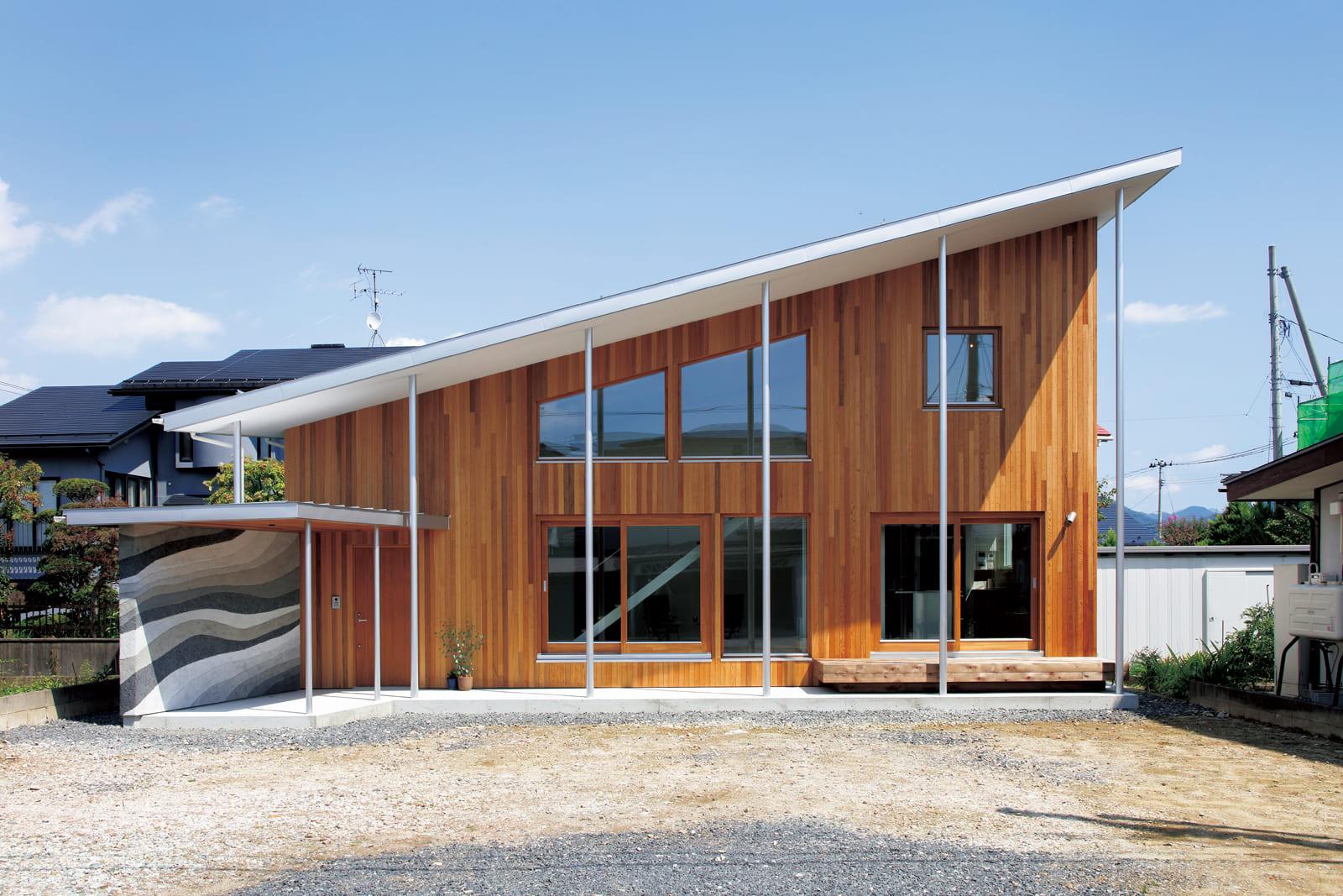 一直線の片流れ屋根と壁面のレッドシダーが美しい。日本古来の版築壁をイメージし、一層一層土の調合を変えて造作された玄関ポーチの土壁が印象的