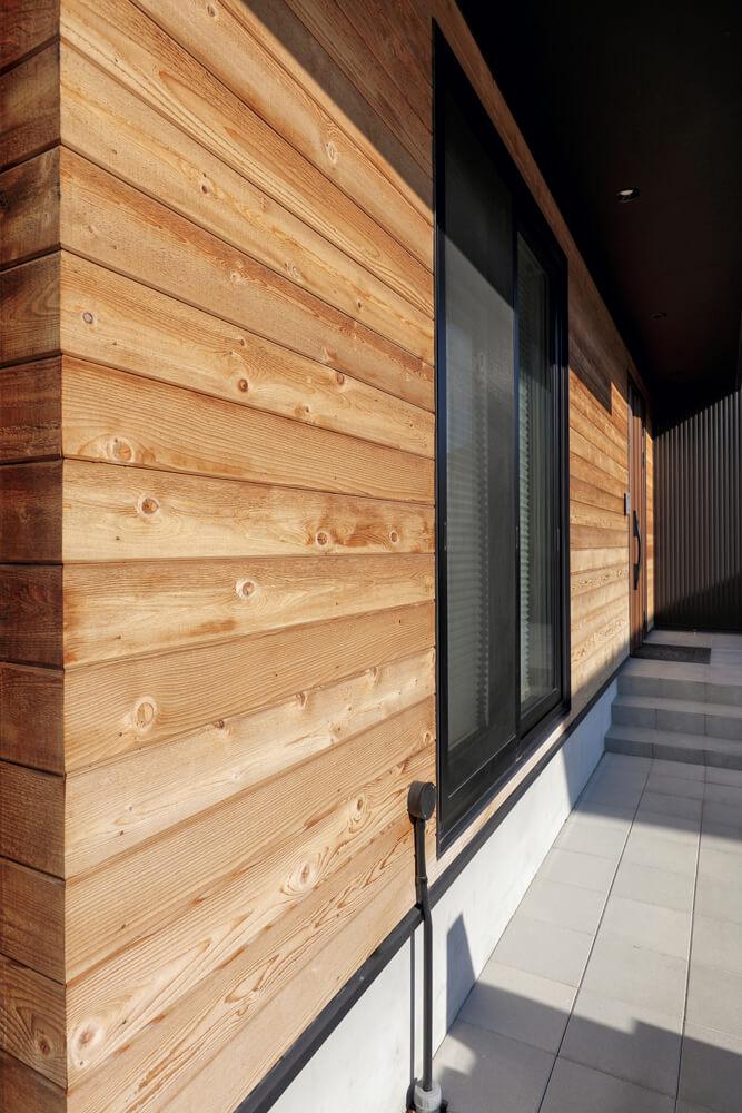 玄関まわりの外壁材はレッドシダーの横張り。わざと粗さを残し経年変化を楽しむ。窓枠は黒で統一しメリハリをつけた