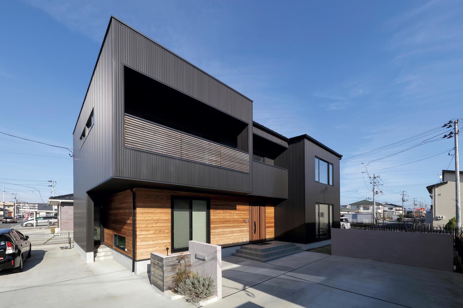 レッドシダーの木目と黒いガルバリウム鋼板のコントラストがシャープな印象を与えるKさん宅。南面の光を存分にとり入れ、太陽光発電パネルも搭載したゼロエネ住宅
