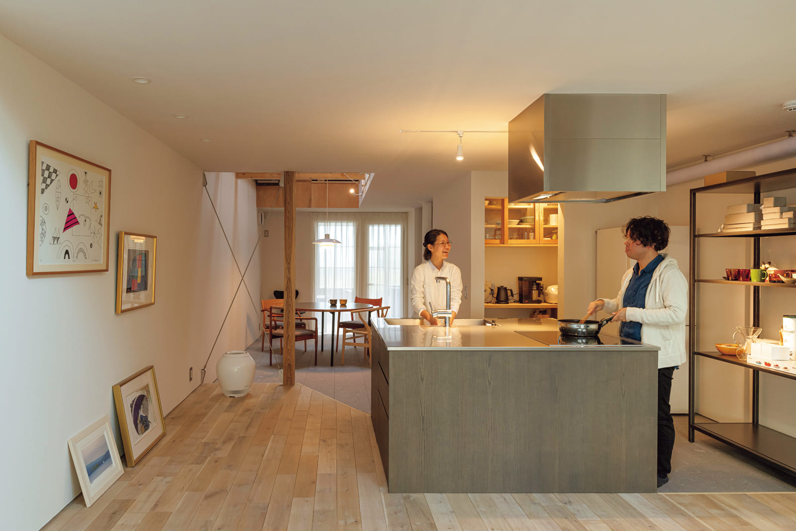 リビングとダイニングをつなぐ正方形のオーダーキッチンは、夫婦2人で会話をしながら料理や片付けができる。パントリーの中の吊戸棚は、元々この家で使われていた棚をリメイクしたもの