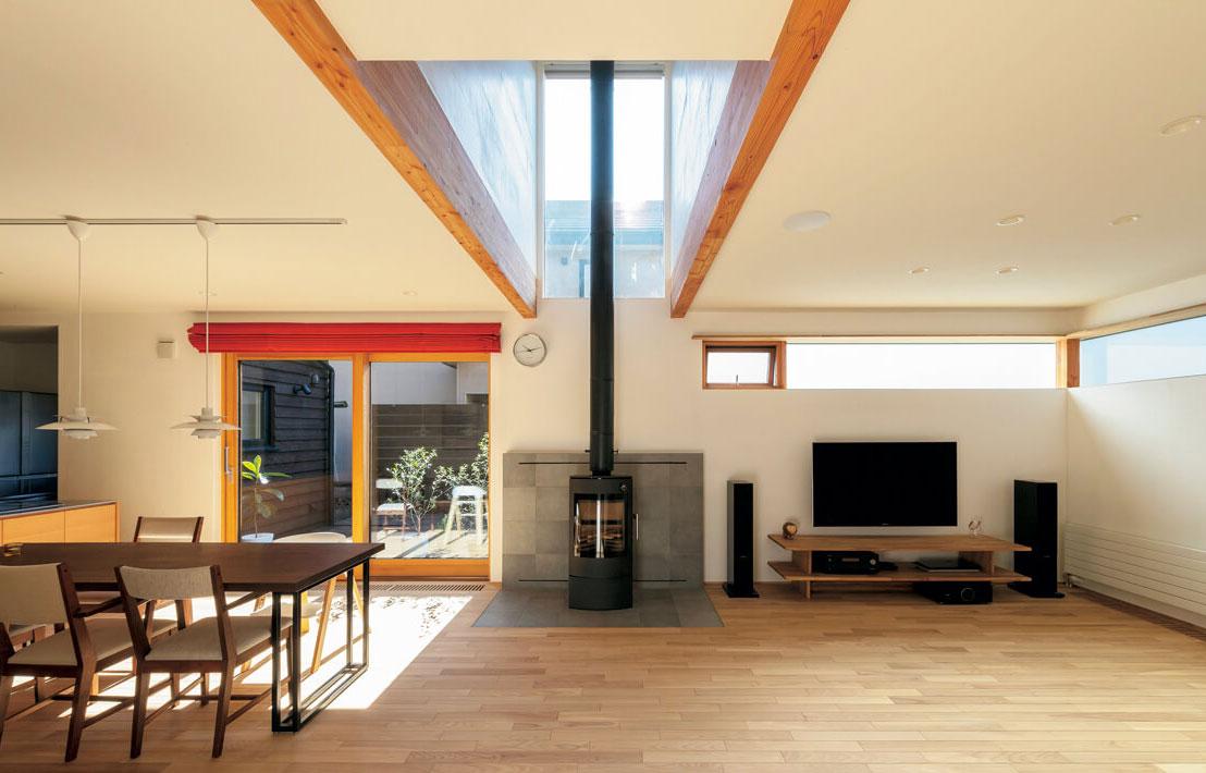 リビングとダイニング・キッチンの間に薪ストーブを設置。薪ストーブの上は吹き抜けになっていて、上へも暖かい空気が回る