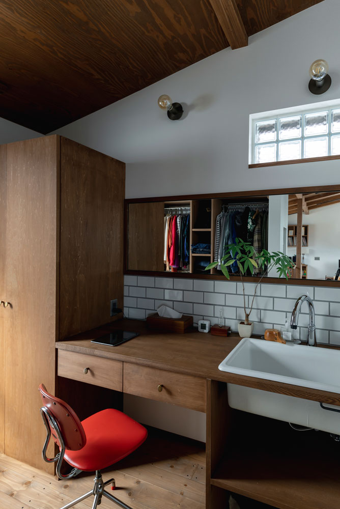 左手の窓と上部のガラスブロックからの光で明るい洗面台まわり。カウンターには奥行きもあり、ちょっとした家事スペースとしても使える