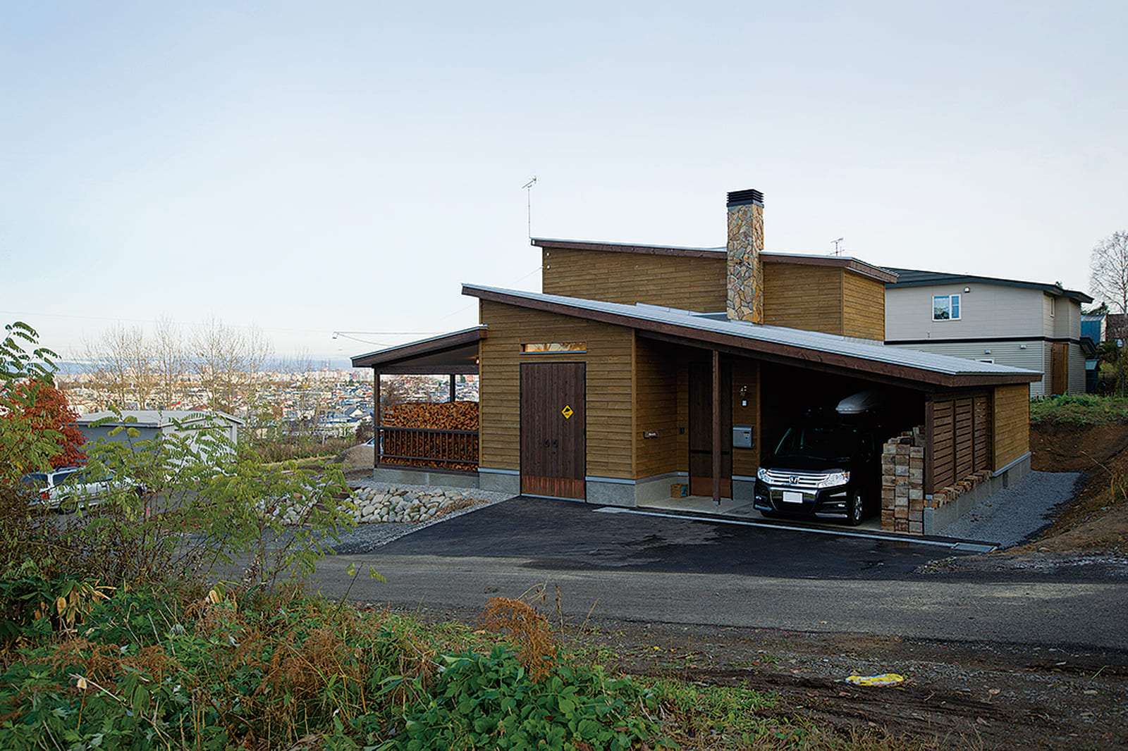 片流れの屋根に煙突、薪かが積まれたデッキや道南スギの外壁と、山小屋風の佇まいが印象的なOさん宅