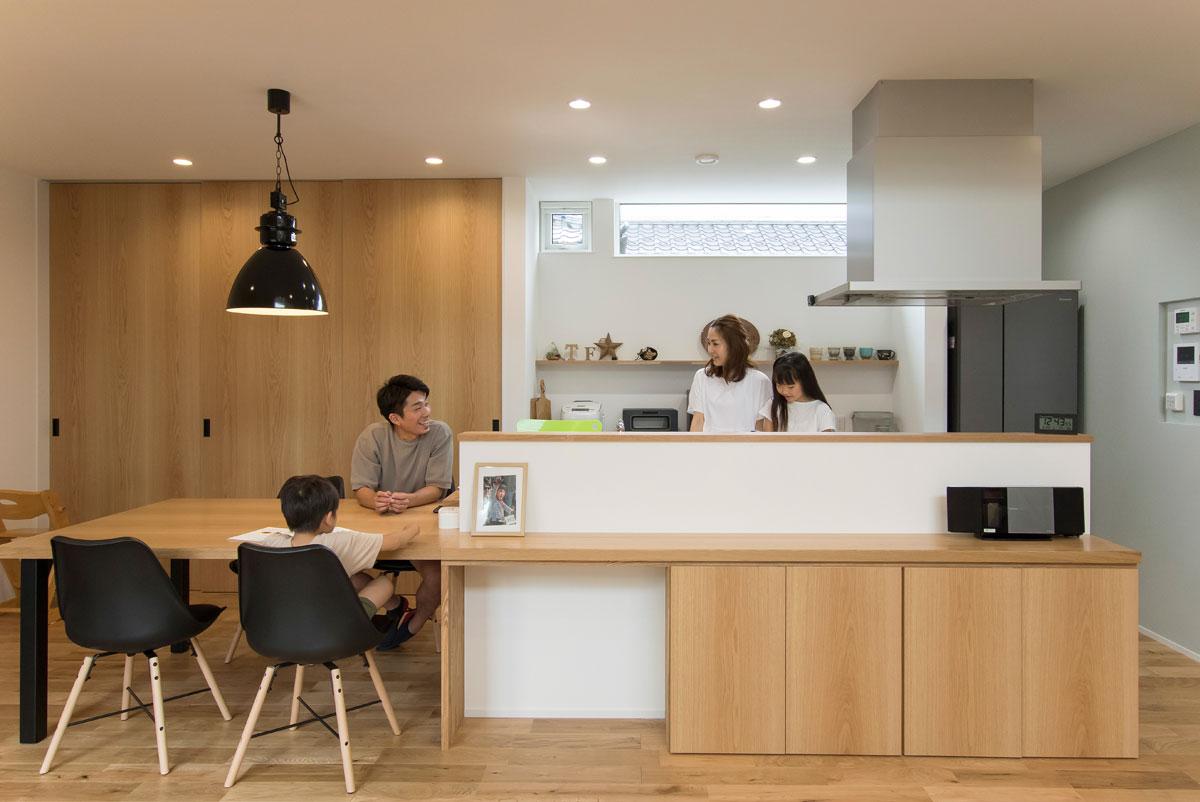カウンターとダイニングテーブルをひとつながりに造作したストレートダイニングのキッチンまわり