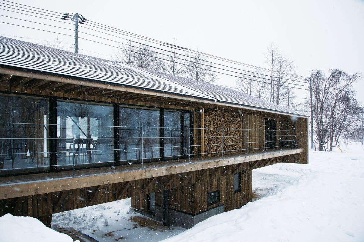 約30mあるデッキには一連の大きな窓と薪棚が設けられ、豪雪に耐えうる橋のような躯体と相まってこの住宅を特徴づけている