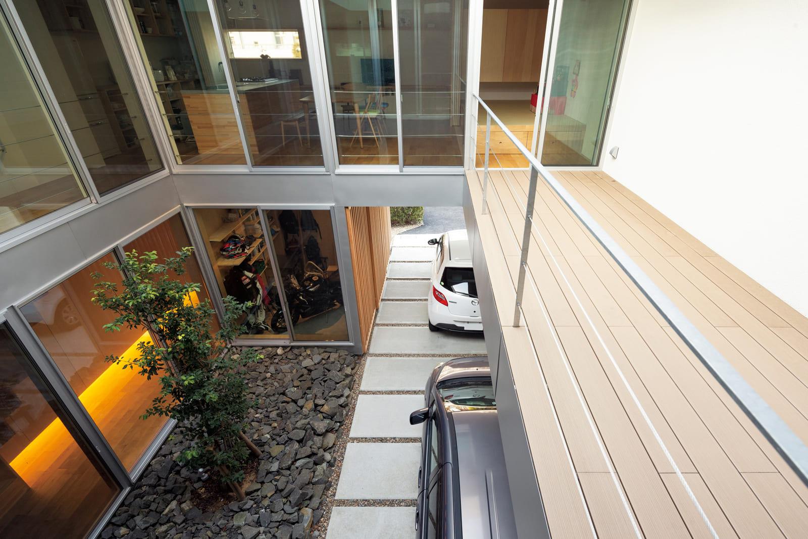 正面の2階部分にLDKが設けられている。その下に、中庭とバイクガレージが見える