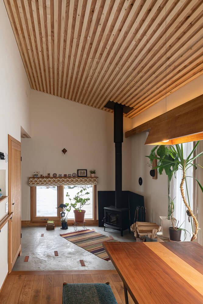 薪ストーブのある広い土間玄関は、4.5帖の洋室と既存の玄関スペースをつなげて実現。ランダムに埋め込まれたレンガタイルがアクセントに。玄関ドアのほか、テラスドアからの出入りも可能なので、薪の持ち運びがスムーズ