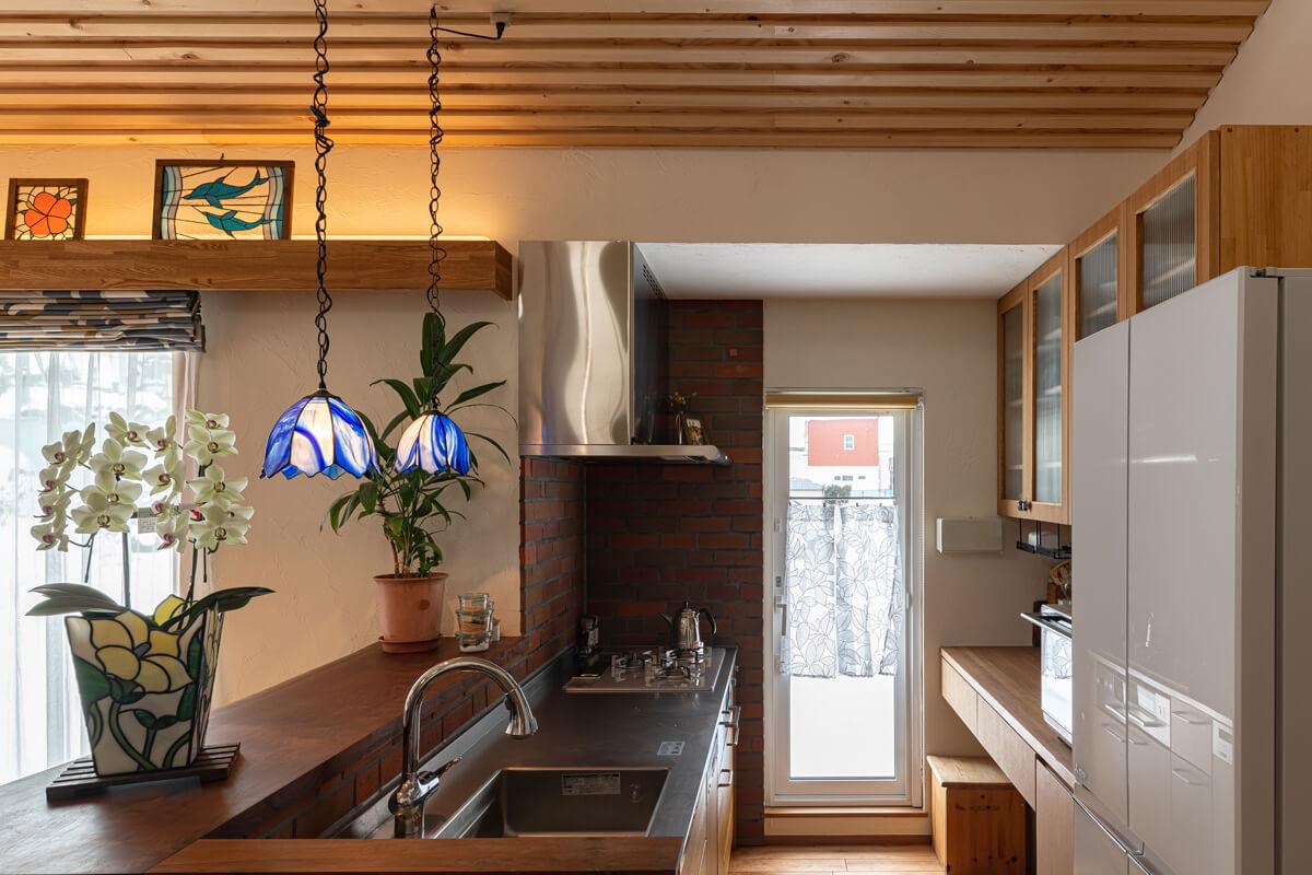ステンドグラスの照明が彩るキッチン。勝手口からウッドデッキに出ることもできる