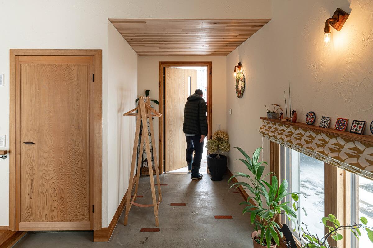 シューズクロークの扉は取り壊された古い家のもので、今では貴重なスギの一枚板。「実はトイレの扉なんです。今、表にしているのが本来は内側になるんですよね。鍵も当時のものなんですよ」とAさん。シューズクロークの中には収納専用の小屋裏スペースがある