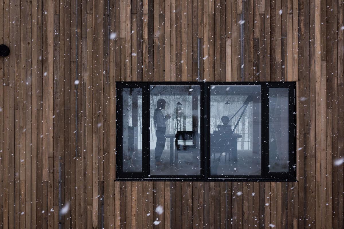 北東側から外観を見る。ダイニングをはさんで重なる窓から抜ける風景が、より一層自然と馴染む