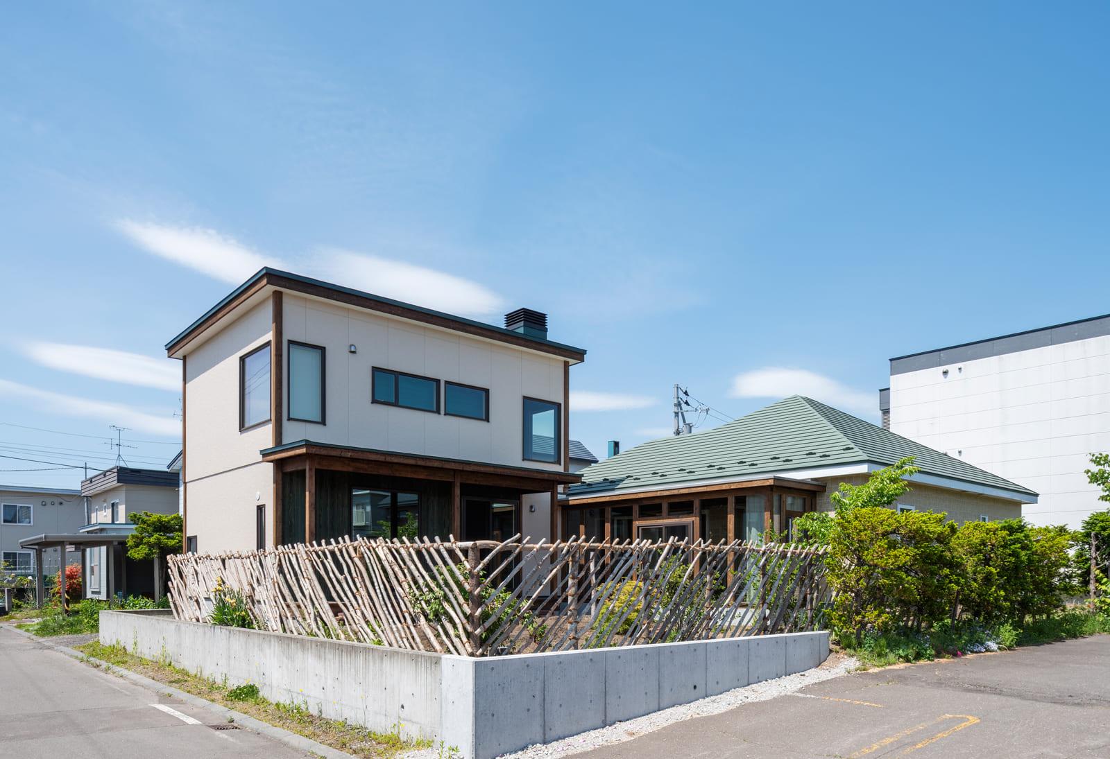 2棟の建物がさりげなく調和するNさんご一家の住まい。手前の木の塀は直接伐採してきてつくったお手製のもの