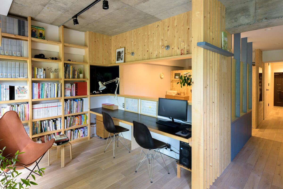 カウンターと壁面収納を一体的にデザインしてつくられたワークスペース。開口を通して寝室の気配も感じられる