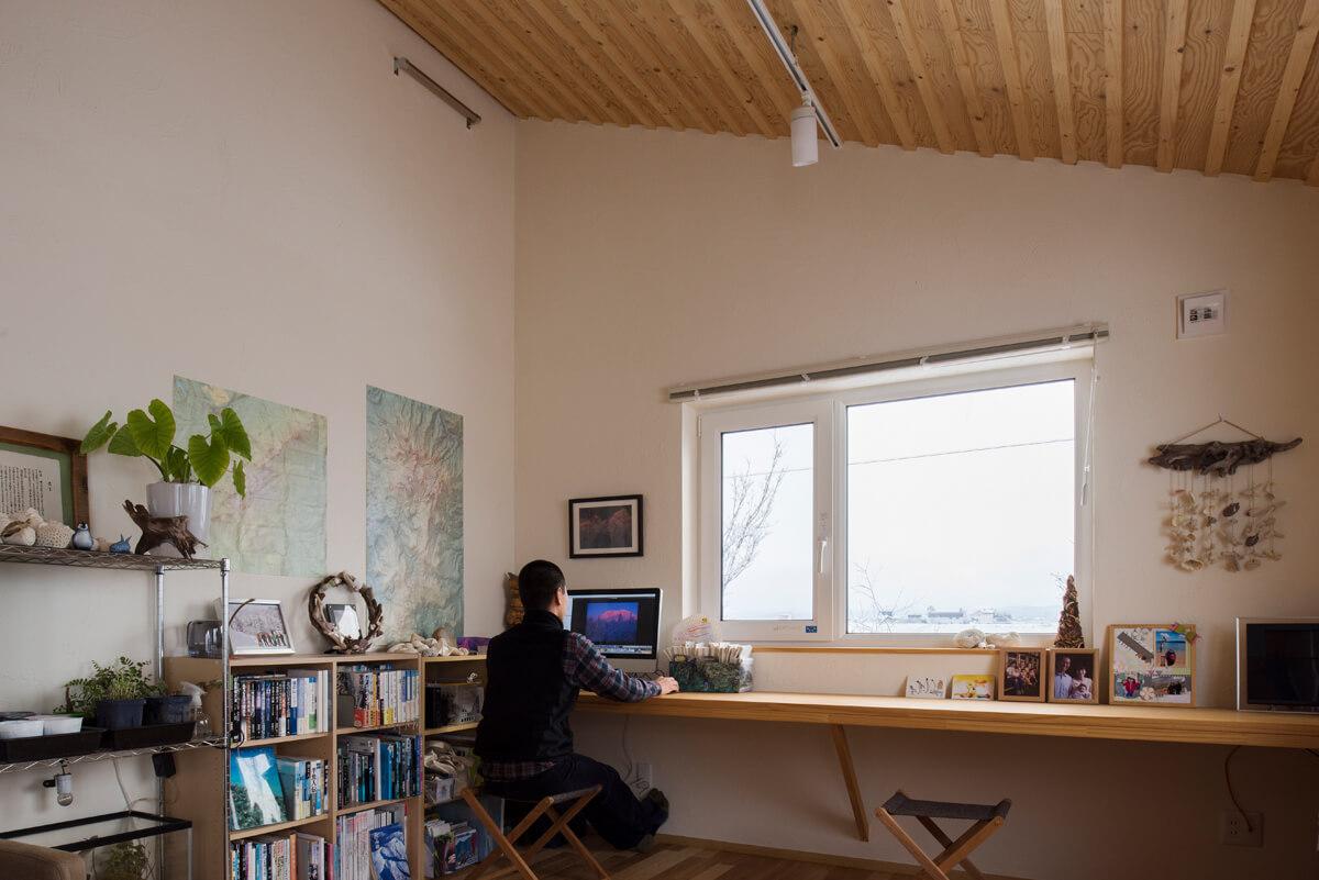 和室だったスペースの壁沿いに長いカウンターを造作してワークスペースに
