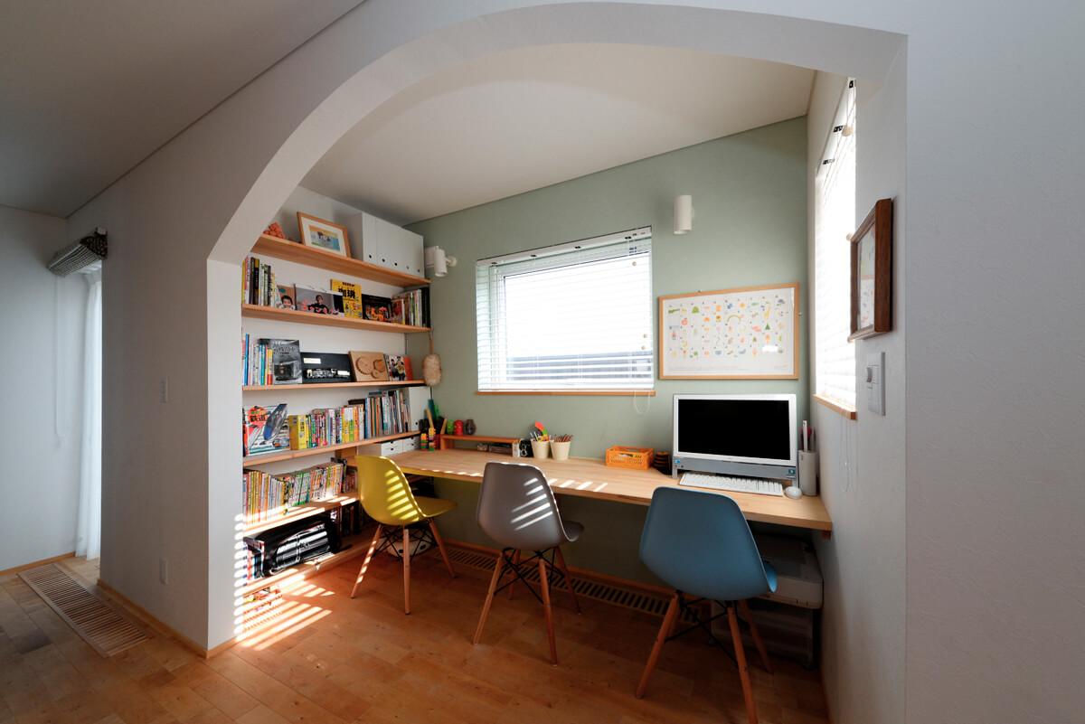 アールの開口と淡いグリーンのアクセントウォール、カラフルなチェアの組み合わせが可愛い空間。壁の一面に造り付けた棚には、本や参考書も収納できる