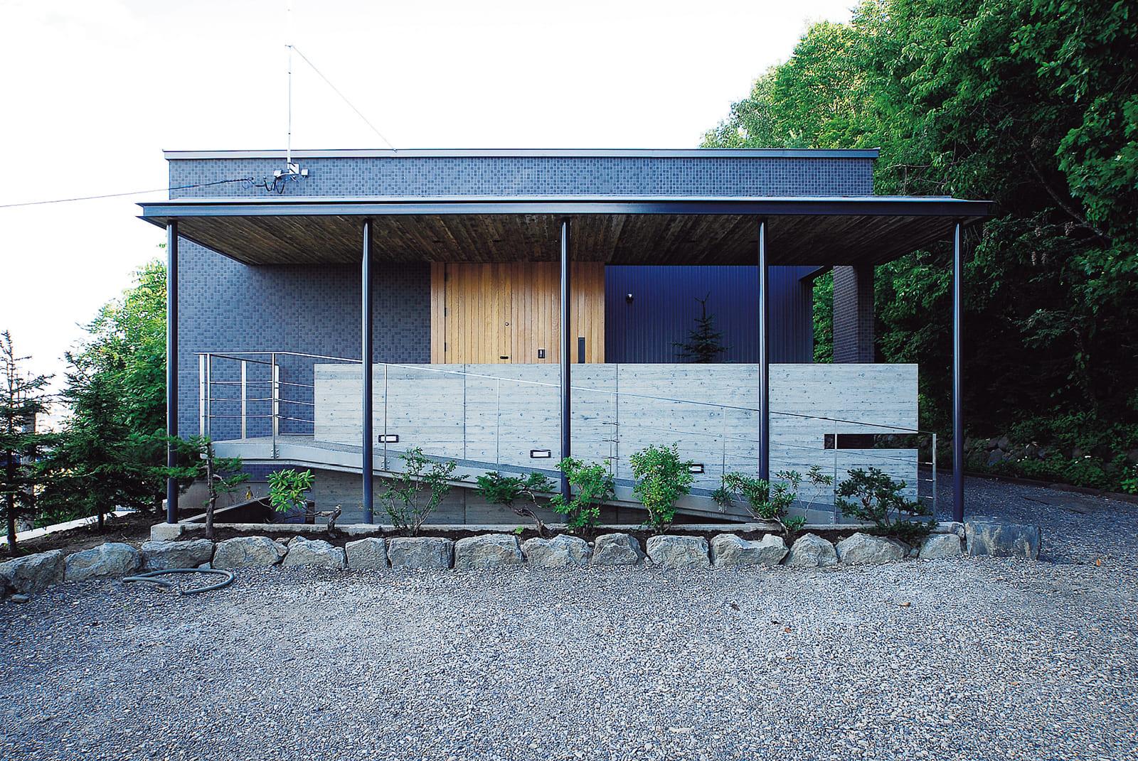 深い軒とコンクリート壁が印象的な外観。玄関ポーチへは階段でもスロープでもアプローチができる