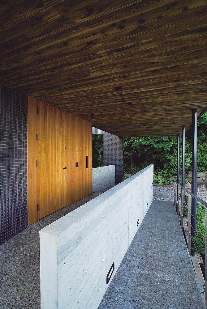 軒天は羽目板仕上げ。低めのコンクリート壁が階段とスロープを仕切る