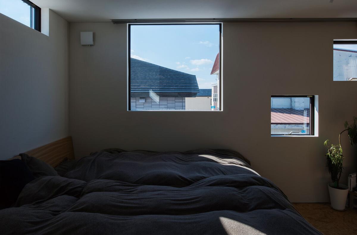 寝室はハイサイドライトや大小の四角い窓がランダムに並ぶリズミカルな空間デザイン
