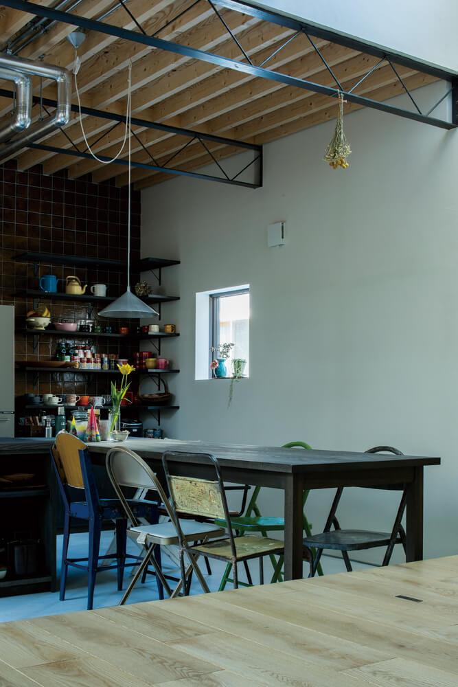 キッチンの作業台と連続したダイニングテーブルは造作でデザインも統一されている。椅子はビンテージものを各所で探して集めたそうだ