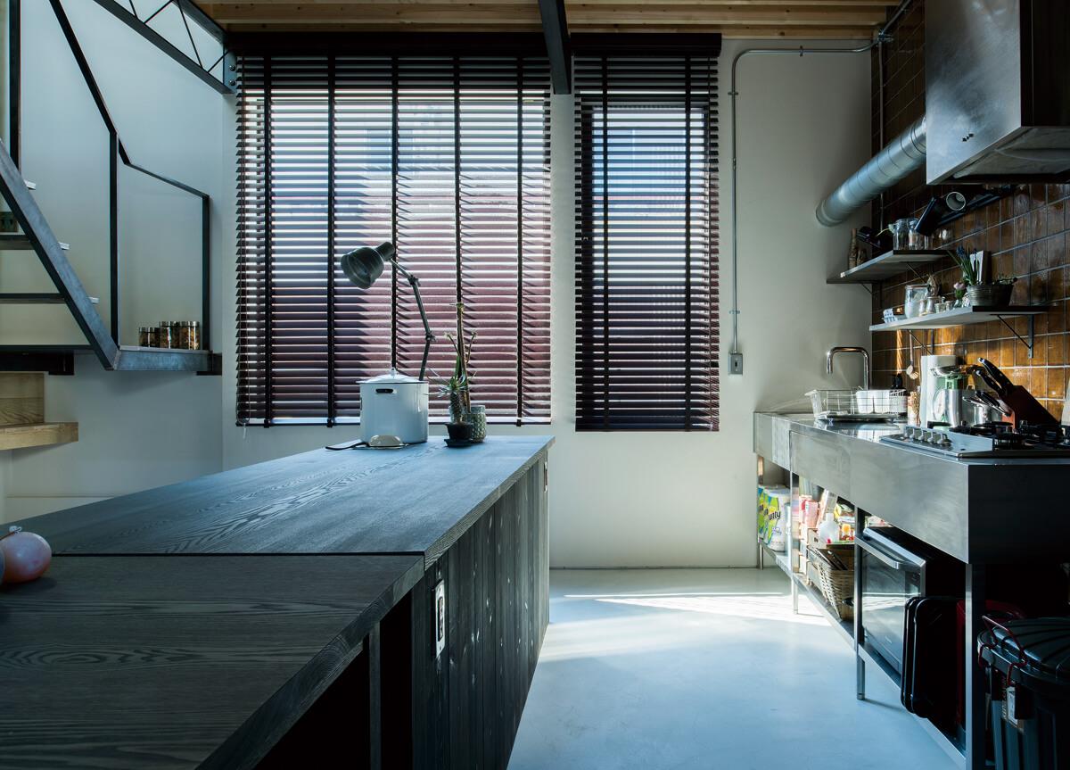 ダイニングからキッチンと南西方向の開口部を見る。吹き抜けの開口部とともに、自然光が十分に入る明るい空間となっている