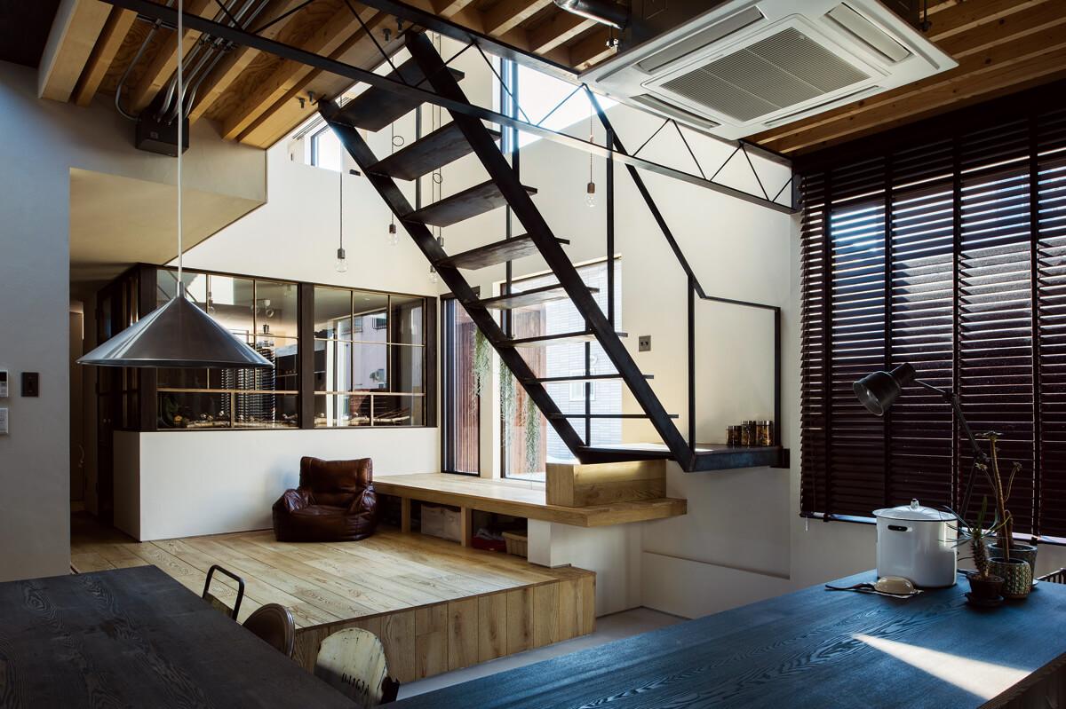 キッチン内からリビング・玄関方面を見る。スキップフロアの床面は、そのまま2階へと伸びるスチールの階段へと続き、変化に富んだ空間構成となっている