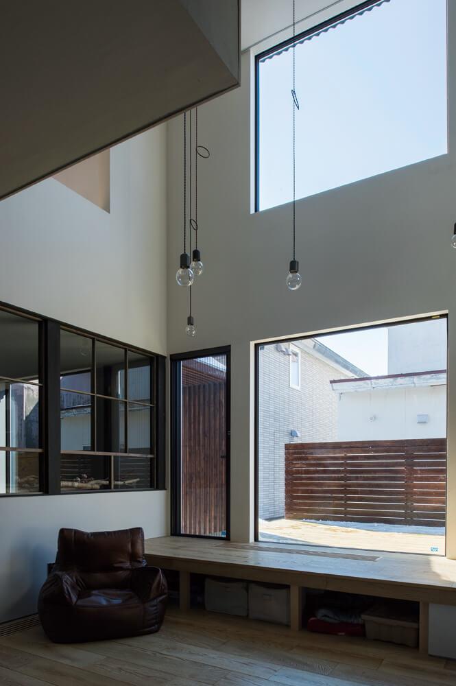 リビングからデッキと玄関方向へ抜ける視線は吹き抜けの効果で開放的な印象を与える