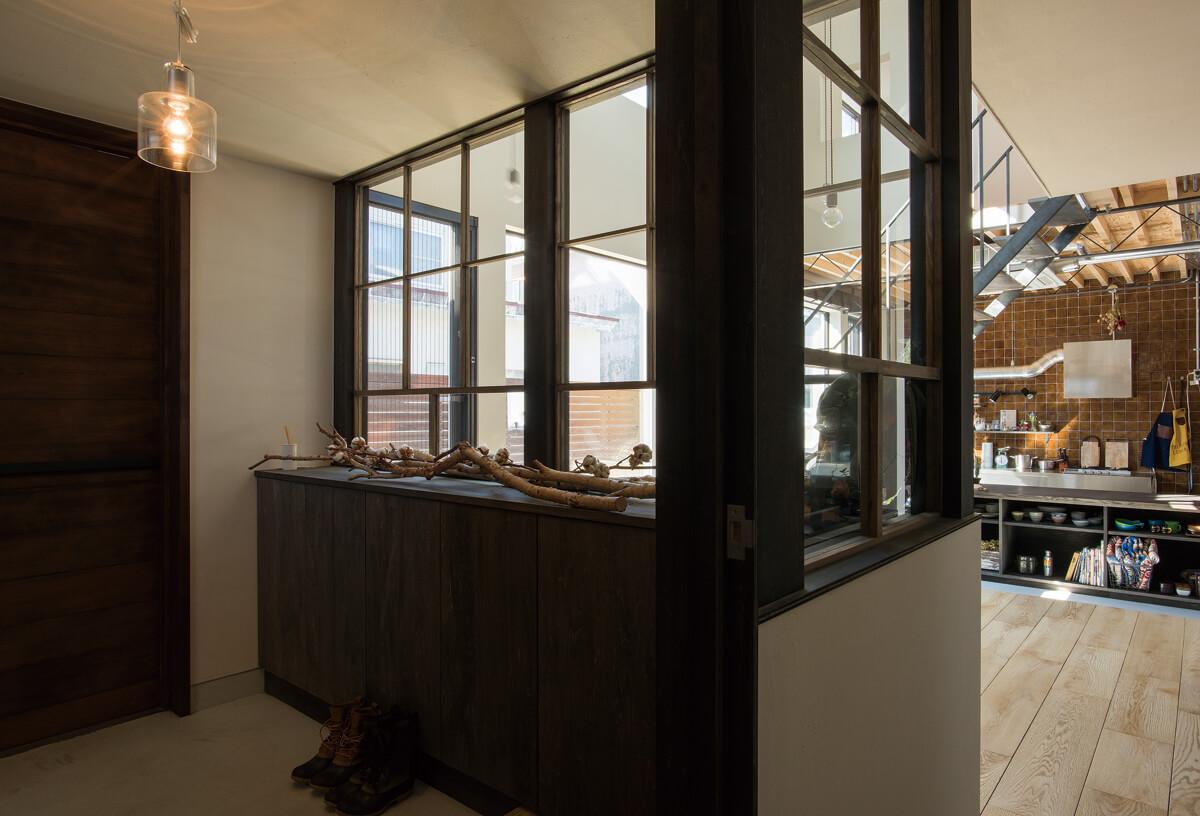 玄関ホールに入るとキッチンが垣間見える。 間仕切り窓の桟がアクセントになっている