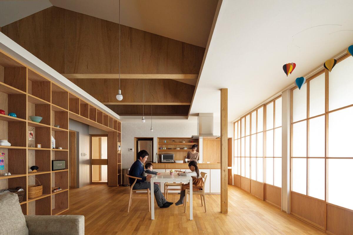 リビングからダイニング・キッチンを見る。天井は屋根なりの仕上げとして高さを確保し、色数を抑えた内装によってシンプルで開放感のある空間となっている