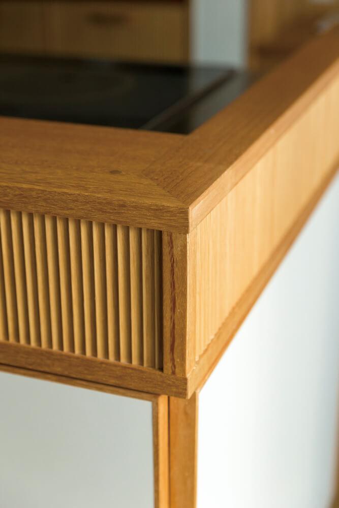 キッチンは同じ木質材料を使いつつも、表面の加工などの細かな部分で違いを見せ、飽きのこないていねいな仕上げとしている