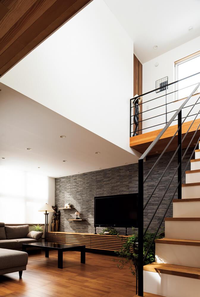 吹き抜けのある階段は、ハイサイドライトからの外光をリビングへ運ぶ。リビングの壁のタイルは、質感豊かな中国のアンティーク石材
