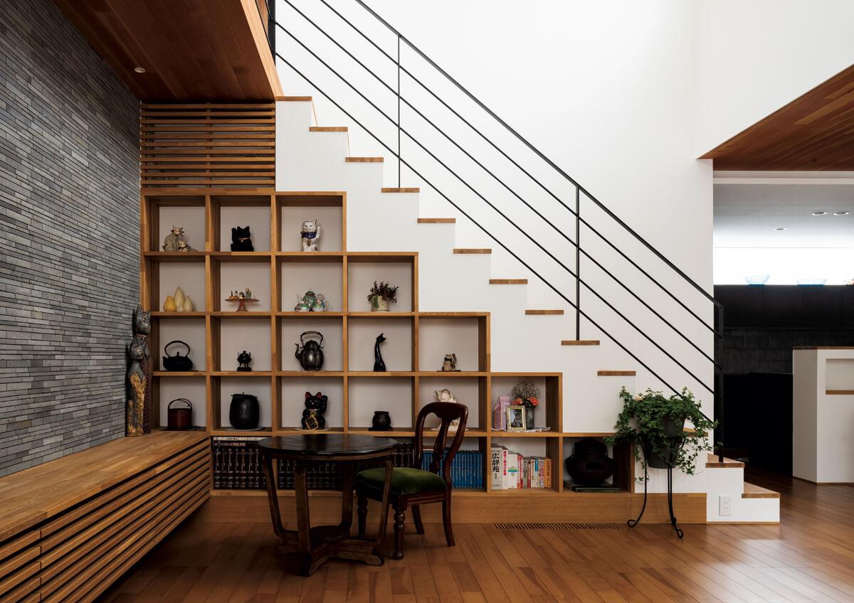 リビングには、階段下スペースを利用した造作棚が設けられ、猫と骨董が好きな奥さんのコレクションが飾られている。ルーバー扉の奥には、エアコンが設置されている
