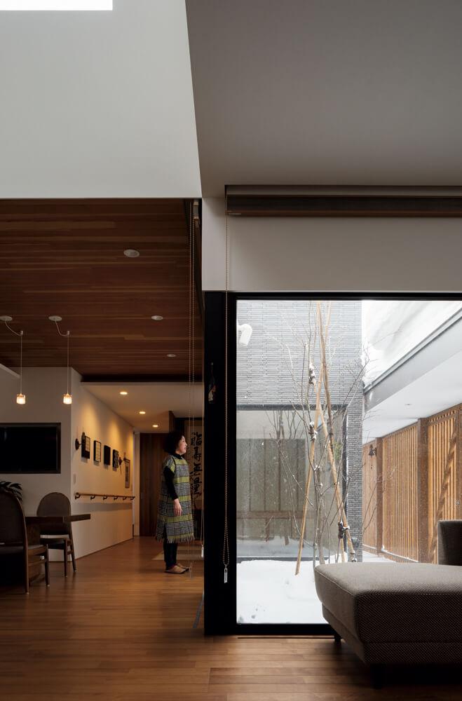 コの字形の大開口によって、中庭スペースと室内空間が一つになり、居住空間に床面積以上の広がり感を創出。開口下には床下放熱器を設置し、窓からの冷気を防いでいる