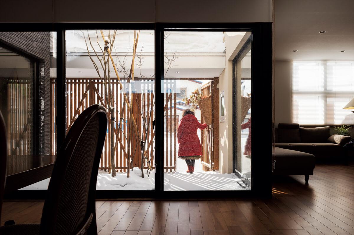 木製ルーバーには外物置のある庭へアクセスできる出入り口も設置。ガーデニングが趣味の奥さんは、このつくりがとても重宝しているそう