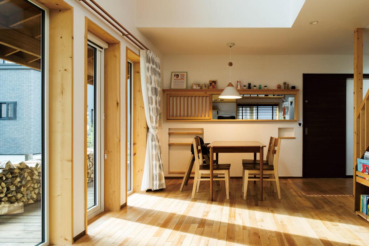 キッチンとダイニングを仕切る壁には横長の窓を設けて、目隠ししながら会話ができるユニークなつくり