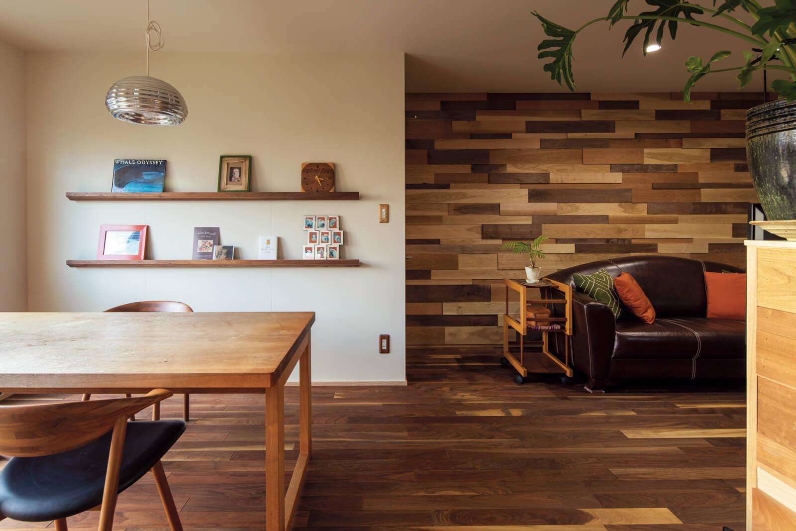 「以前の住まいから使っていたウォールナットのダイニングテーブルは、経年変化で白くなってきました。無垢材はこうした月日の変化が楽しいですよね」とSさん。ペンダントライトも以前の住まいから引き継いだもの。壁の造作棚には、ギンくんの成長過程が伺える写真が並んでいる