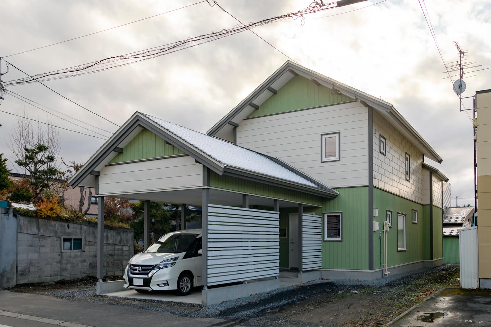 グリーンとホワイトをベースにした明るい雰囲気の三角屋根の外観