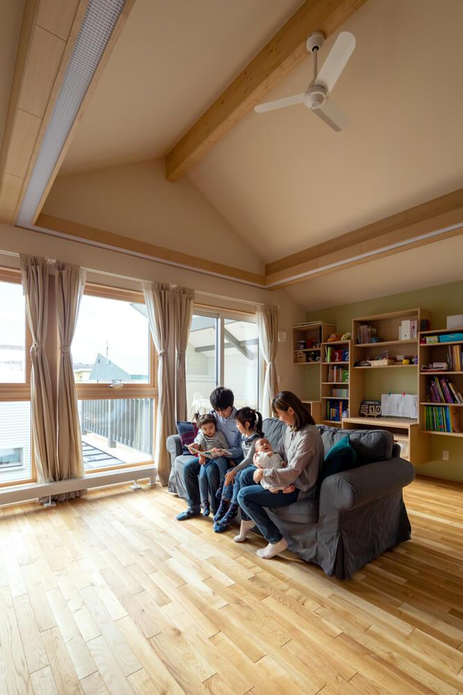 2階は勾配天井がもたらす開放感と、無垢フローリングが与える温もりが心地よい家族が集うLDK。壁一面の収納は、子どもたちの机やランドセル置きになる便利な可動棚