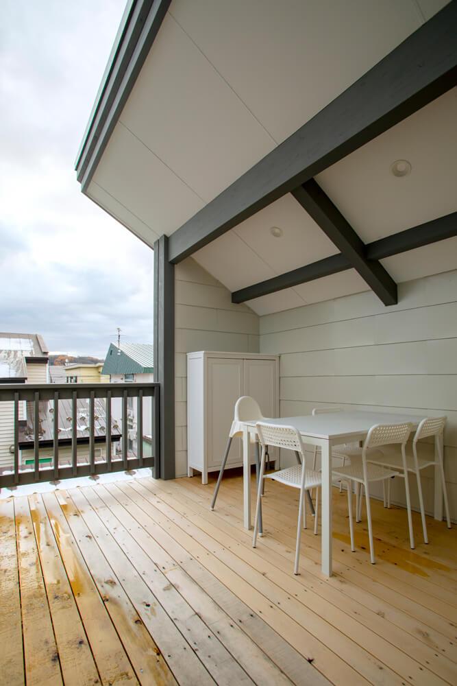 屋根が陽射しや雨から守ってくれるウッドデッキには、バーベキューなどが楽しめるようテーブルと椅子を設置