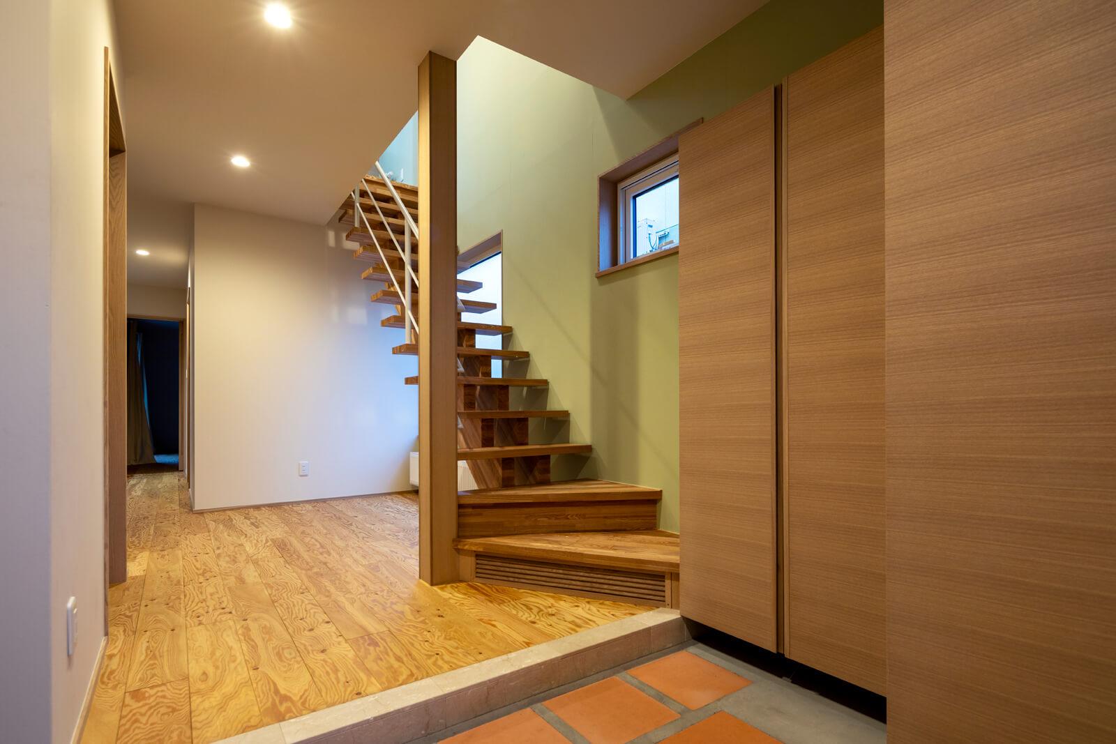5人家族には嬉しい広い玄関スペース。玄関の床はテラコッタタイルを採用。階段から降りてくる光も心地よい