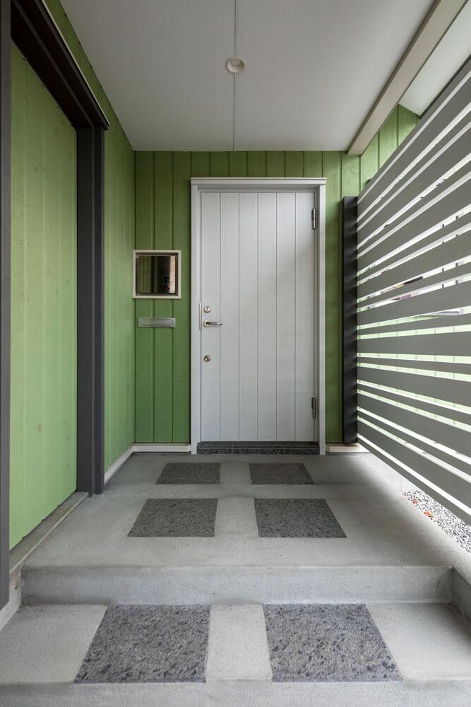 グリーンの外壁に、白い木製ドアが映える
