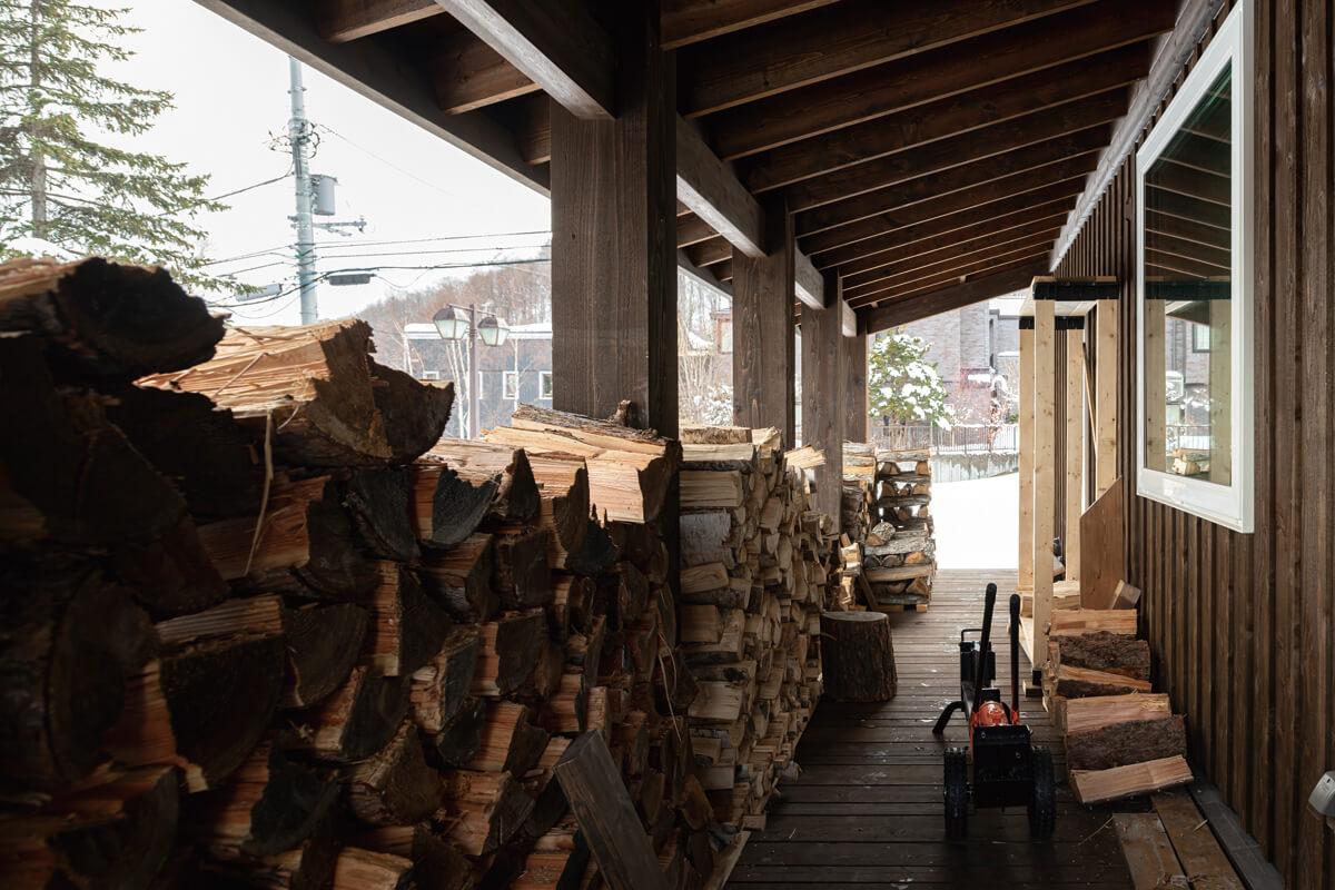 軒を広く張り出したウッドデッキには2シーズン分の薪が並ぶ