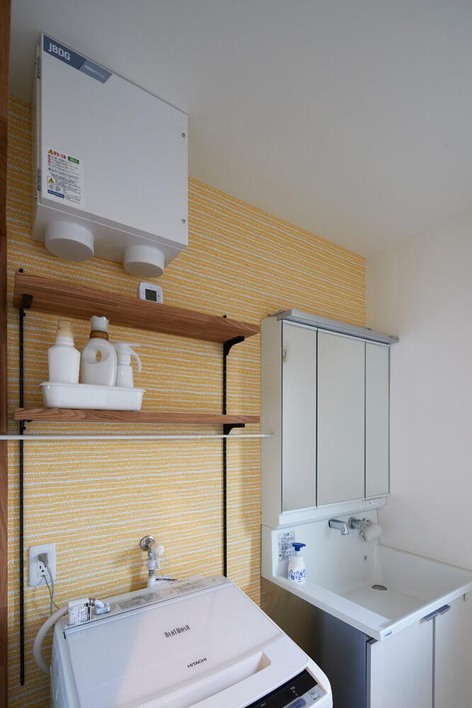 洗面脱衣室の壁の一面もイエローに。風水も意識しながら配色を決めたという
