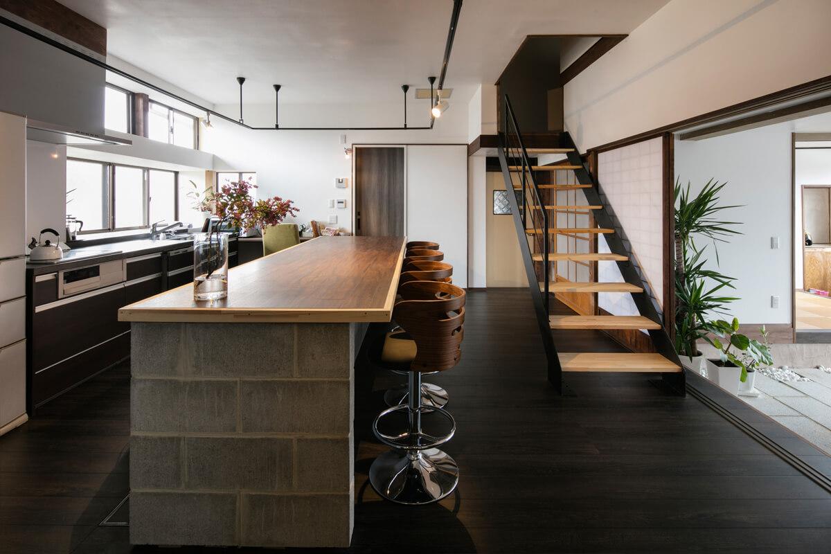 木やコンクリートブロック、アイアンといった異素材を組み合わせてデザインされた広いキッチンには、大きなカウンターテーブルを造作。階段は、ご夫妻の寝室へとつながる