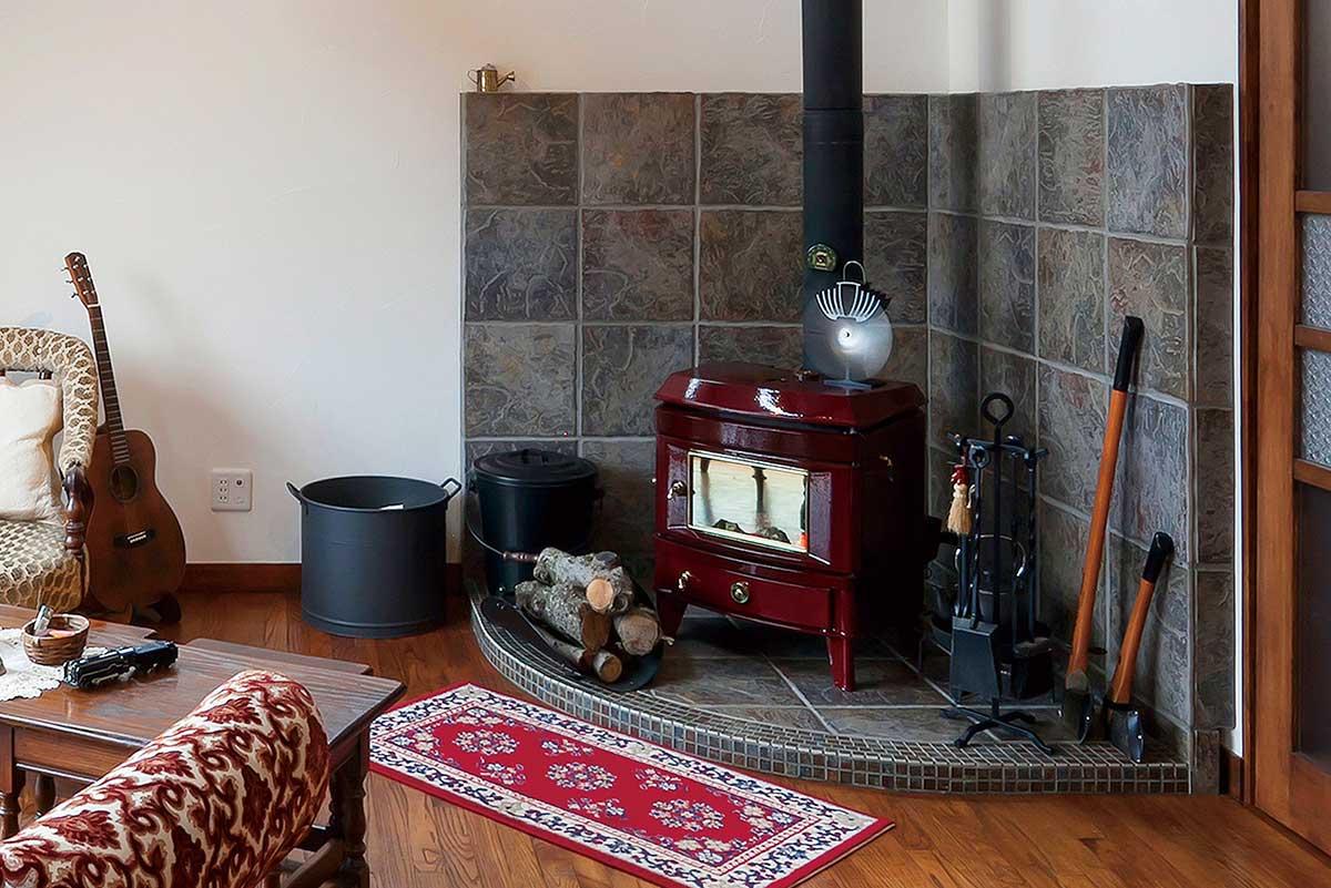 よく見るとさまざまな色が混ざりあった鮮やかな石調のタイルを炉壁と炉台に使用。赤色の薪ストーブとエキゾチックなデザインの家具やラグにぴったり