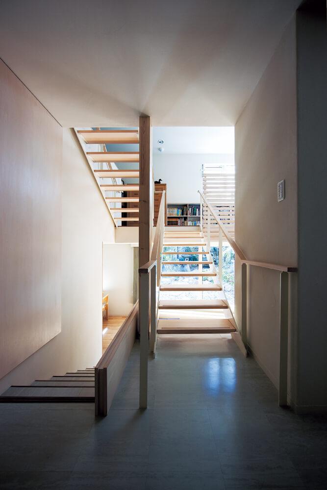 玄関を入り、ホールから階段を見る。半階下にはメインのLDK、上にはプライベートスペース。全ての空間がゆるやかに結ばれている